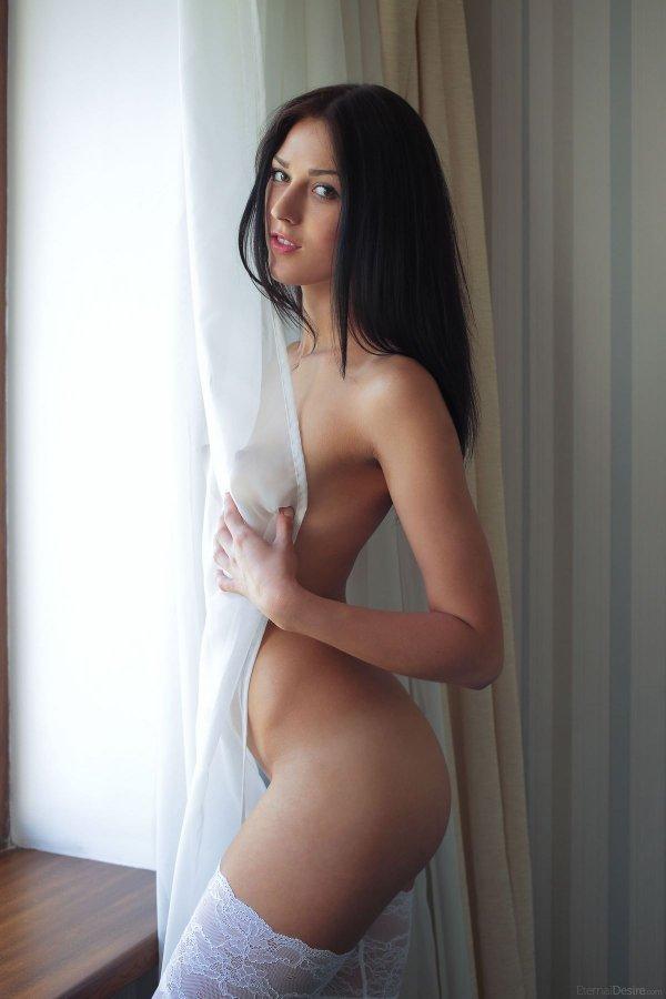 Брюнетка в белых чулках стоит возле окна