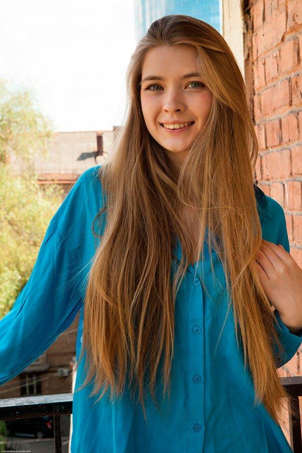 Девушка с длинными волосами позирует в голубой блузке