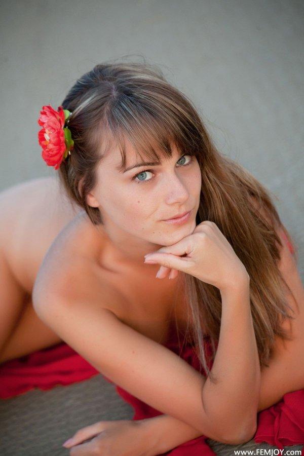 Девушка с красным цветком в волосах голая на природе