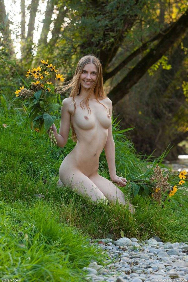 Голая девушка с букетом возле лесного ручья