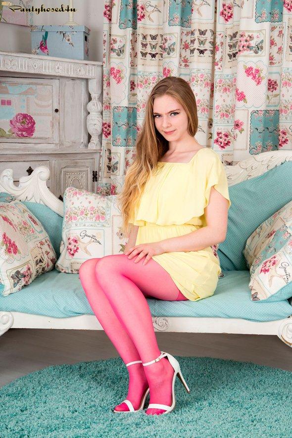 Очаровательная блондинка с длинными волосами позирует в розовых колготках