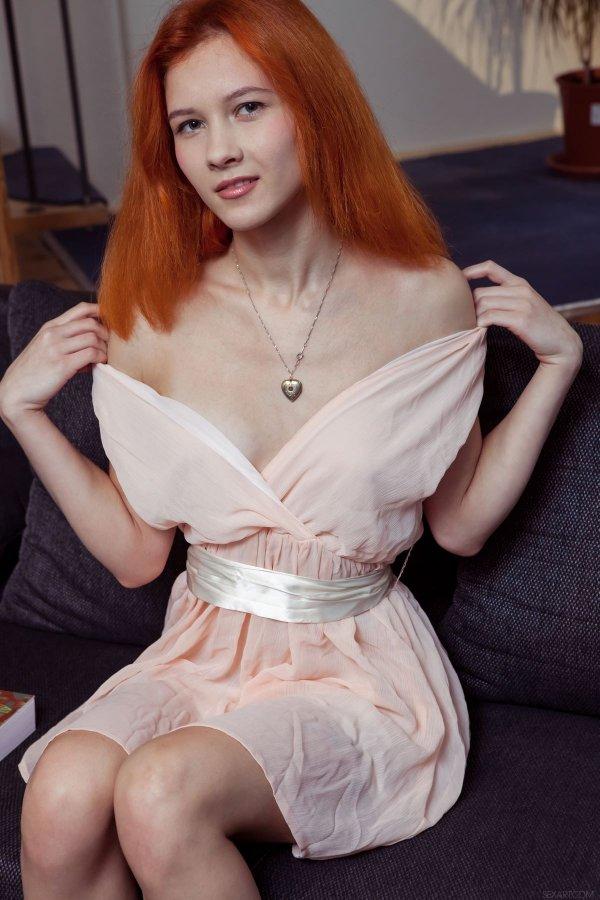 Рыжая девушка снимает платье